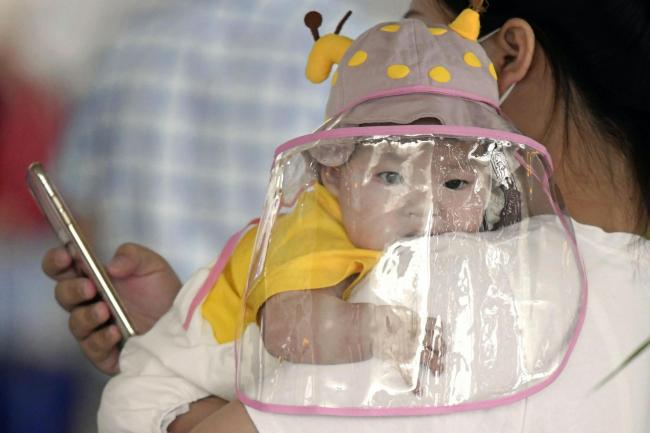 A baby with a face shield waits to board a plane at an airport in Wuhan, China