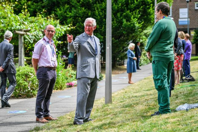 VISIT: The Prince of Wales gestures to crowds of hospital staff watching from a distance. Picture: Ben Birchall/PA Wire
