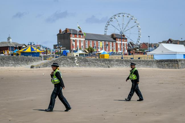 Police officers walk on promenade
