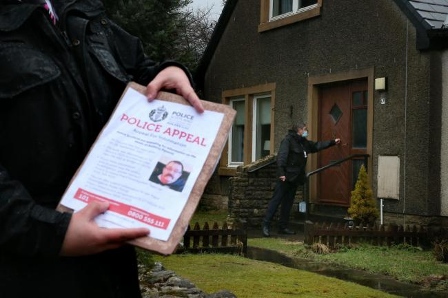 Police officers distribute posters and leaflets in Tyndrum, Stirlingshire, appealing for information on Tony Parsons