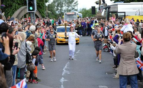 Joanne Simon carries the torch over Abbey Bridge and up Cheltenham Road