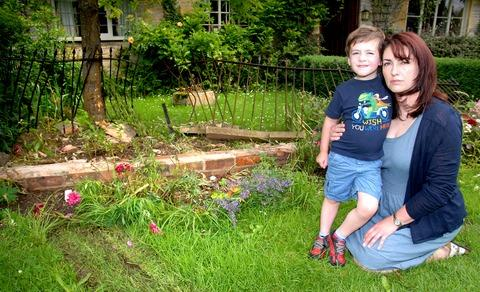 CRASH: Lisa Davis with her son Jamie in her front garden after a car ploughed into it. Picture: Nick Toogood. 27080302