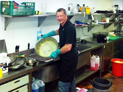 A pan caked with scrambled eggs holds no fear for Dormy House Hotel manager turned kitchen porter David Field