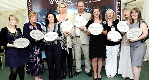 SMILES SAY IT ALL: These winners from last year's Welcome Awards event display their plaques.
