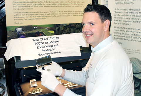 Councillor John Campion inspects the hoard of coins that was discovered on Bredon Hill.