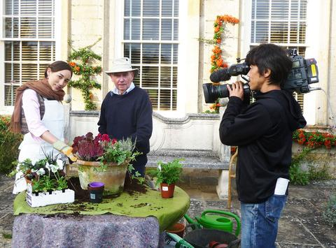 Japanese model Hanae with head gardener Paul Nicholls being filmed by an NHK cameraman at Bourton House Gardens.