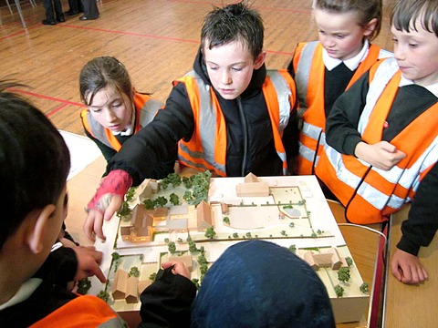 BIG PLANS: Children examine a model of the revamp to their school in Overbury.