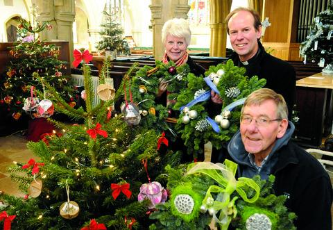 FESTIVE: Pictured at the Christmas Tree Festival at St Edwards Church, Stow, are Susan Bratlin, Rev Martin Short and Derek Magson.