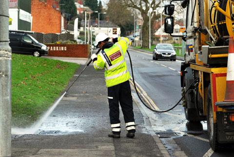 Clearing drains after flooding in Hylton Road, Worcester