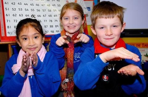 Swell Primary School pupils taking part in the world record Sign2sing. From left, Claire Antiojo, aged seven, Ellie Keegan, nine, and Arthur Fletcher, six.