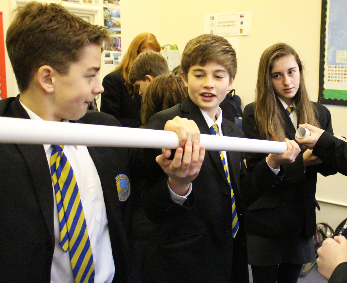 Students Johnnie Parker, Robbie Lord and Faye Conisbee exercise their teamwork skills with other Year 9 pupils considering how they might pipe clean water across a disas