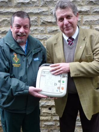 Dick Tracey, of SCAS, with Cllr Mark Booty, Cabinet Member for Health, holding an AED