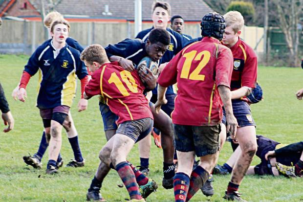 Cotswold Journal: STRONG TACKLE: Action from the clash between Evesham under 15s (red) and Westcliffe High School from Essex. James Thompson halts the tourists' progress. Picture: PENNY BENNETT.