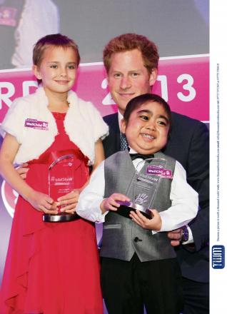 Prince Harry on stage at the WellChild Awards 2013 with winners of the inspirational child category, Madison Kirk (6) and Jonathan He (6). Picture by Carl Hewlett/TWM - Thousand Word Media Ltd.