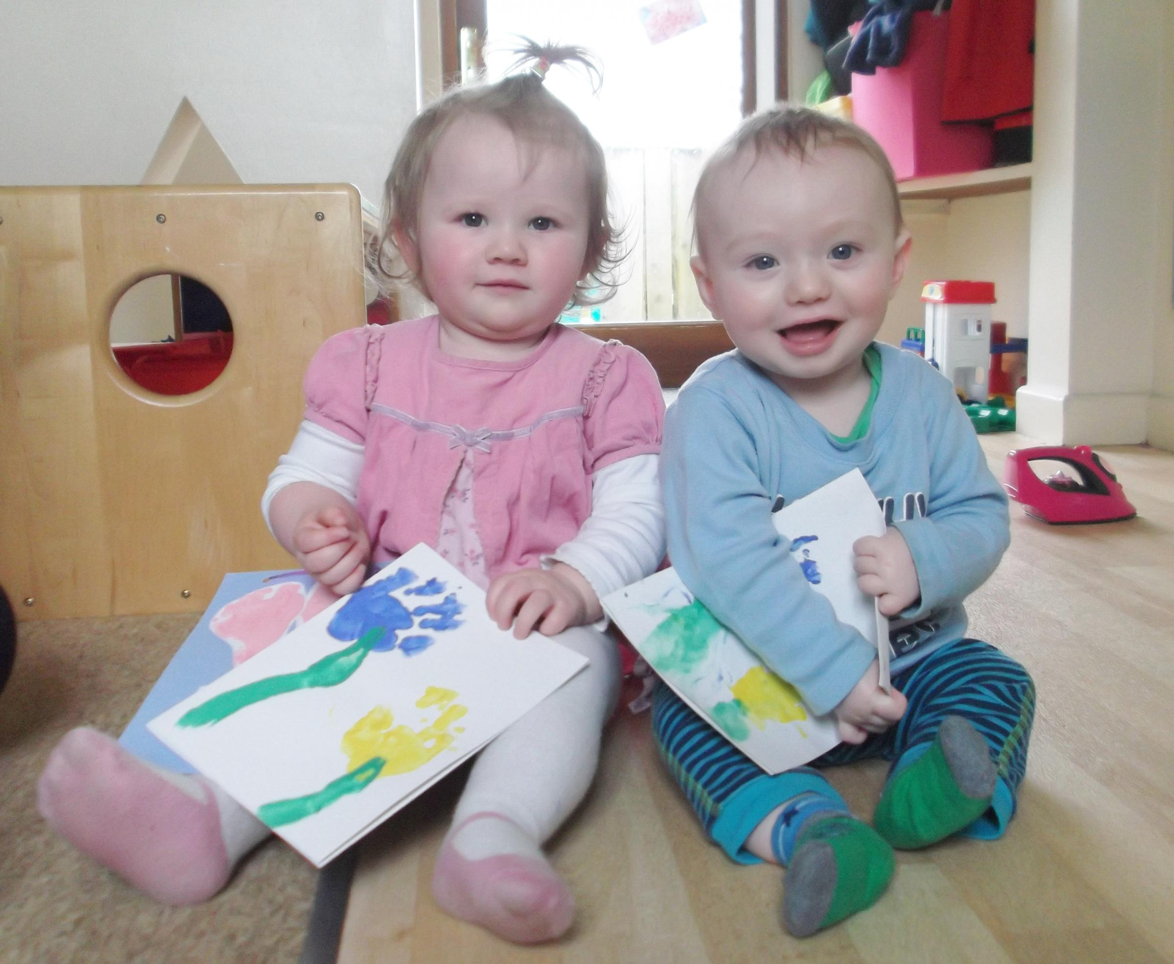 toddlers Jessie Evans (aged 14 months) and Harry Smith (aged 7 months) showing off their hand-print Mother's Day cards.