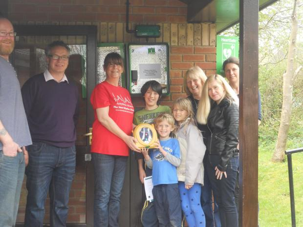 Caroline Holmes of Arrhythmia Alliance with village children Tom, Joe and Lily Lewis and Lucy Oliver (right, black leather jacket )