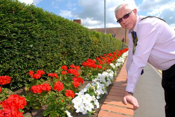 Mayor of Shipston-on-Stour Philip Vial with one of the town's flower beds that were targeted by thieves. Stolen flowers have since been re-planted. Picture by Nick Toogood. (7686417)