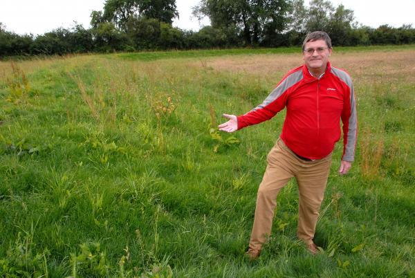 SAFE: Cllr Robert Dutton inspects a flood bund in Moreton. Cash to finish the defences has been secured. 2814644402.