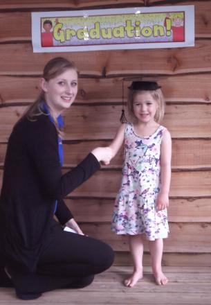 Four-year-old Grace Conway receiving her graduation certificate from Duty Manager Katherine Williams
