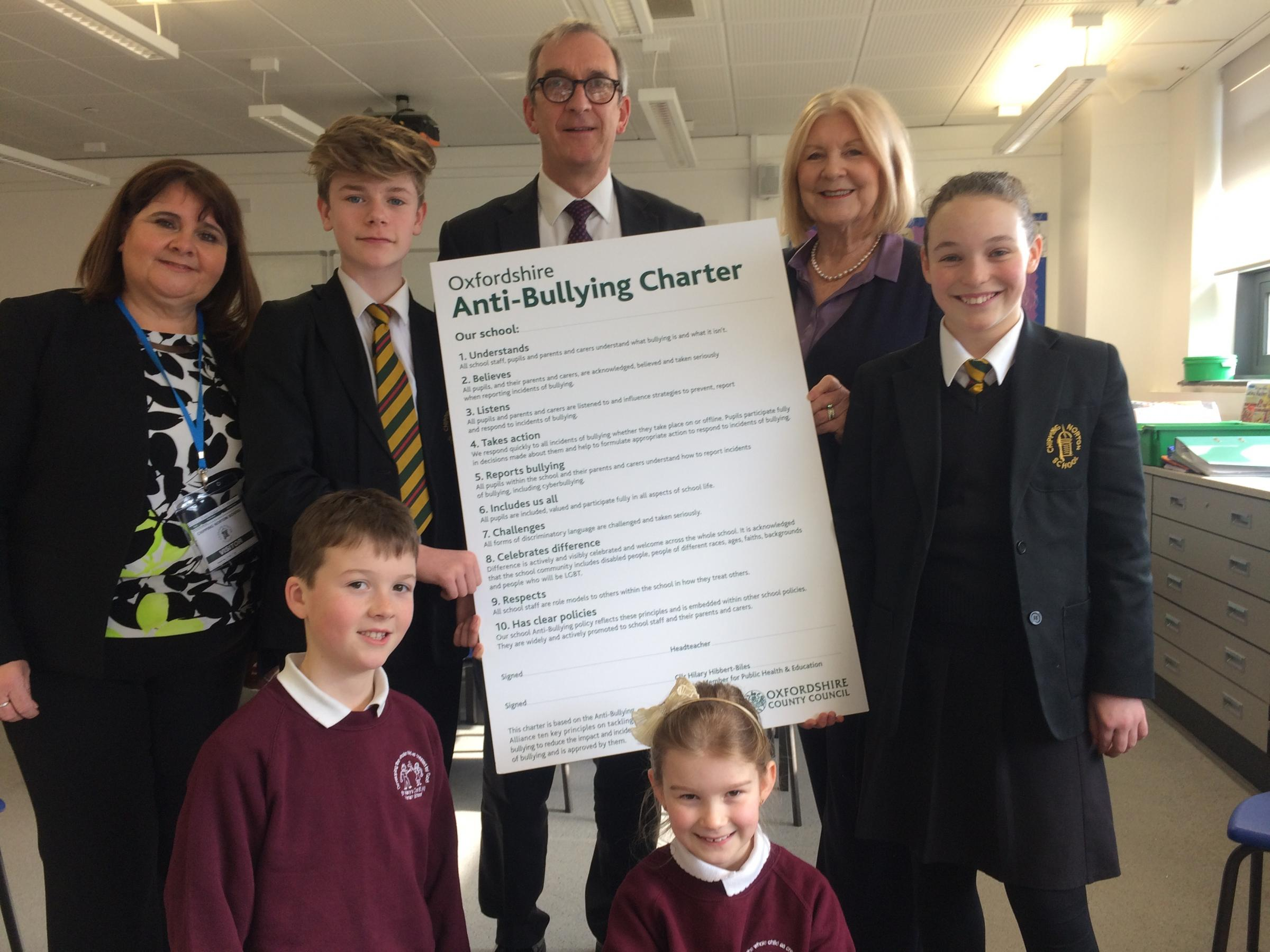 PLEDGE: Oxfordshire County Council's cabinet member for Education and Public Health Hilary Hibbert-Biles (second right) presents the anti-bullying charter to Chipping Norton School headteacher Simon Duffy (back, centre) and St Mary's Primary School he