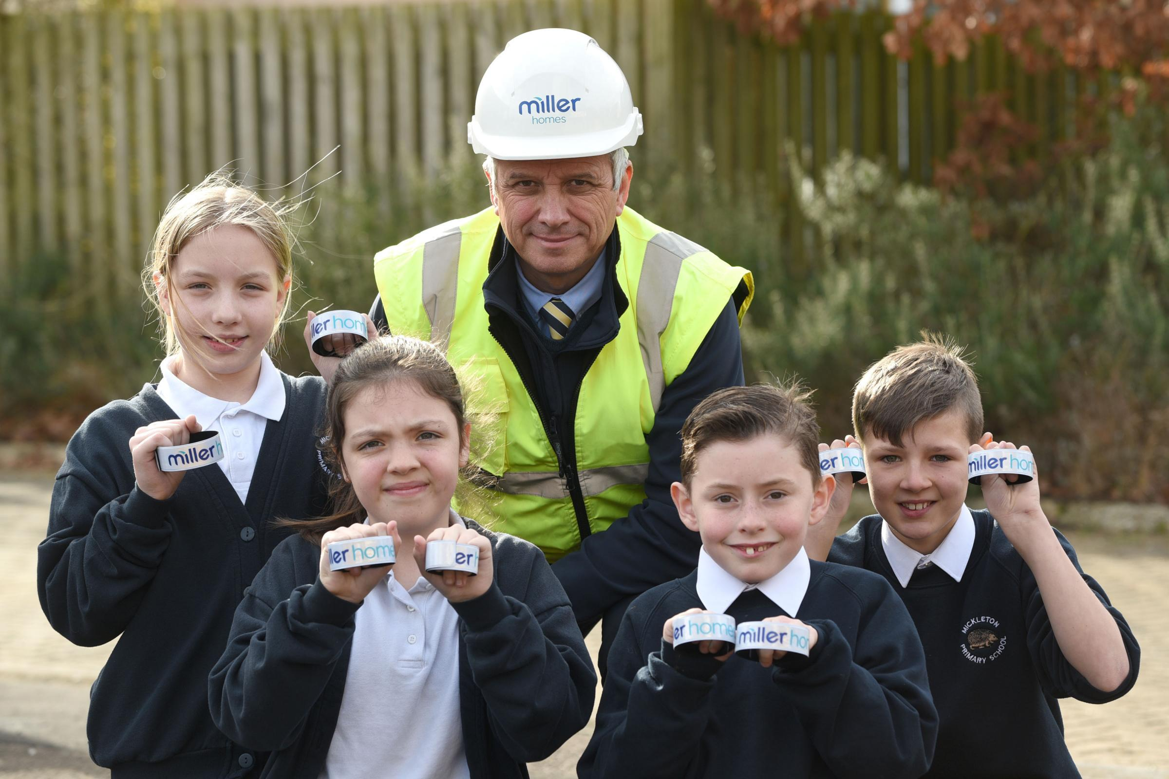 Gary Kuzmicz, health safety and environmental manager at Miller Homes Midlands, presenting reflective snapbands to the pupils of Mickleton Primary School following their health and safety talk.