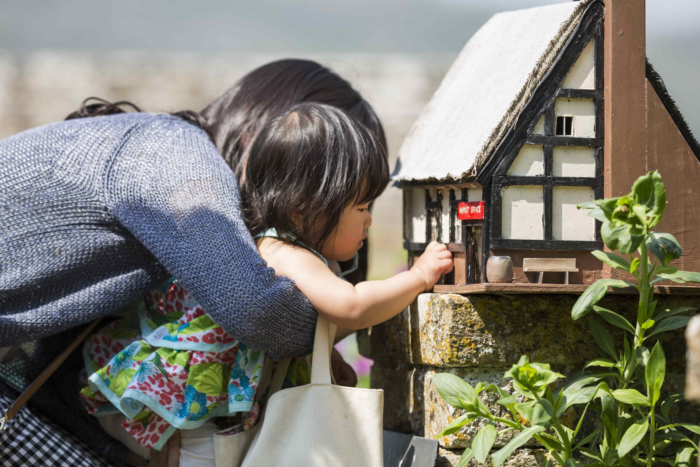 Visitors exploring Wolf's Cove model village at Snowshill Manor and Garden, Gloucestershire
